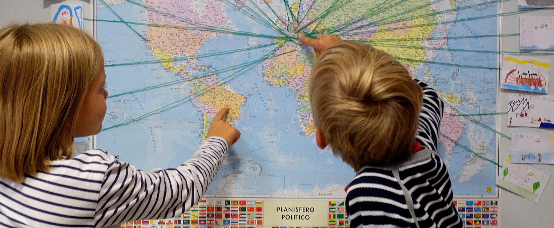Studenti della scuola primaria bilingue indicano su un planisfero
